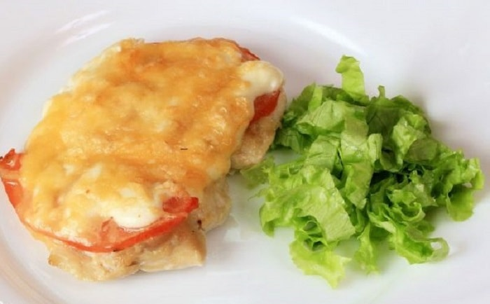 Готовое блюдо мяса по-французски с помидорами и сыром в духовке