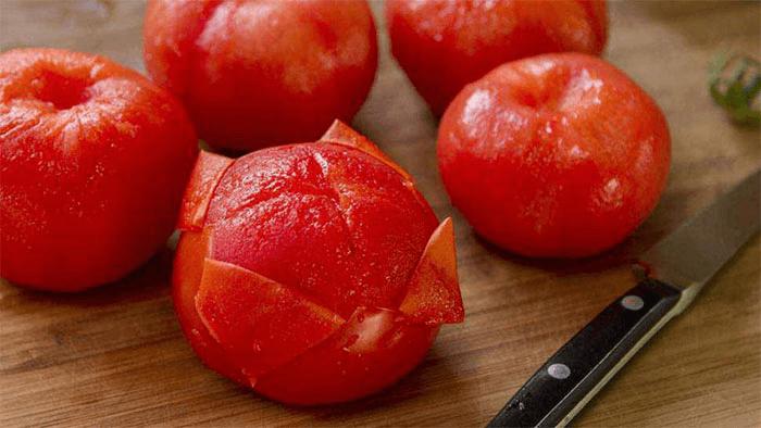 Удалить кожуру и место черенка, нарезать помидоры.