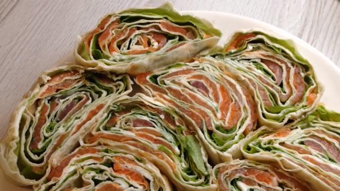 Рулет из лаваша с красной рыбой и листьями салата – картинка